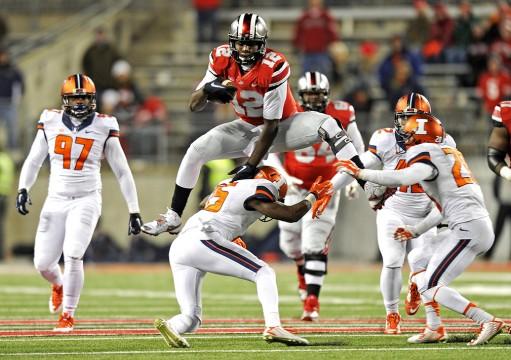 OSU redshirt-sophomore quarterback Cardale Jones (12) hurdles a defender during a game Nov. 1 against Illinois at Ohio Stadium. OSU won, 55-14.  Credit: Ben Jackson / For The Lantern
