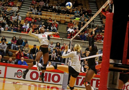 OSU junior middle blocker Tyler Richardson (23) leaps to spike a set by OSU senior setter Taylor Sherwin (8) during a match against Maryland on Nov. 7 at St. John Arena.  Credit: Madelyn Grant / Lantern photographer
