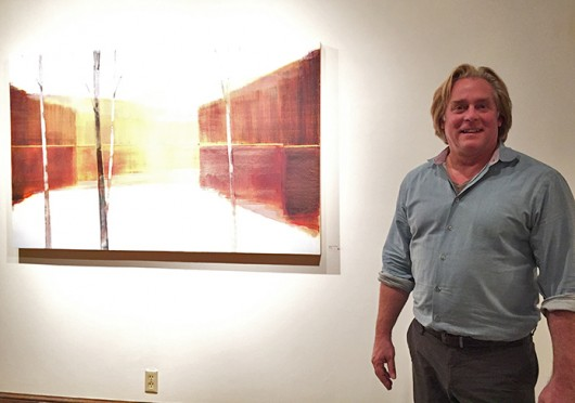 James Keny — co-director of the Keny Galleries — stands in front of a piece by late OSU professor Edmund Kuehn. The artist's work will be displayed at the Keny Galleries in German Village until Dec. 31. Credit: Anbo Yao / Lantern reporter