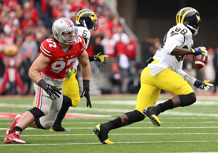 Then-sophomore defensive lineman Joey Bosa (97) chases after then-redshirt senior Michigan quarterback Devin Gardner (98) during a game against Michigan on Nov. 29 at Ohio Stadium. OSU won, 42-28. Credit: Lantern file photo