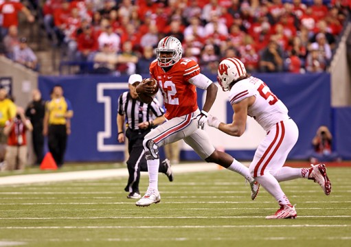 Redshirt-sophomore quarterback Cardale Jones (12) carries the ball during the Big Ten Championship Game against Wisconsin on Dec. 6 in Indianapolis. OSU won, 59-0. Credit: Mark Batke / Photo editor