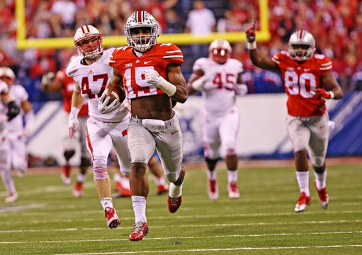 Sophomore running back Ezekiel Elliott (15) breaks away on an 81-yard touchdown run during the Big Ten Championship Game against Wisconsin on Dec. 6 in Indianapolis. OSU won, 59-0. Credit: Mark Batke / Photo editor