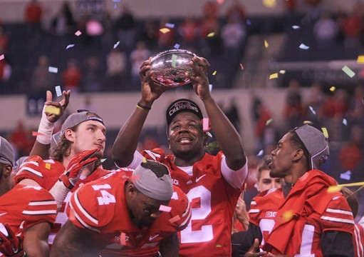 Redshirt-sophomore quarterback Cardale Jones (12) lifts the Stagg Championship Trophy into the air following the Buckeyes win against Wisconsin in the Big Ten Championship Game on Dec. 6 in Indianapolis. OSU won, 59-0. Credit: Chelsea Spears / Multimedia editor
