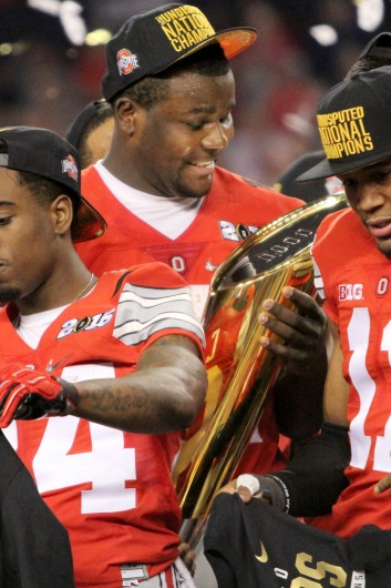 Redshirt-sophomore quarterback Cardale Jones holds the College Football Playoff National Championship trophy after OSU's 42-20 win against Oregon in the title game on Jan. 12 in Arlington, Texas.  Credit: Mark Batke / Photo editor