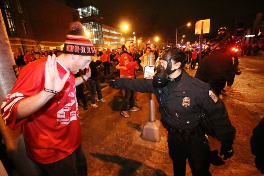 A Columbus Police officer attempts to control a fan on North High Street in the early morning of Jan. 13. Credit: Yann Schreiber / Lantern reporter