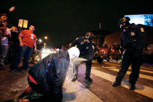 A Columbus Police officer uses pepper spray on an Ohio State fan on North High Street near OSU campus in the early morning of Jan. 13. Police responded to fan riots following OSU's 42-20 national championship victory against Oregon on Jan. 12. Credit: Yann Schreiber / Lantern reporter