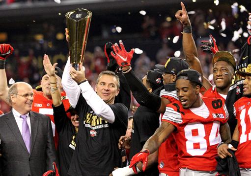 Coach Urban Meyer lifts the 2015 College Football Playoff National Championship Trophy following a 42-20 win against Oregon on Jan. 12 in Arlington, Texas. OSU won, 42-20. Credit: Mark Batke / Photo editor