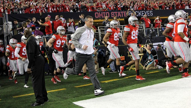 Coach Urban Meyer leads the OSU football team onto the field at AT&T Stadium before the College Football Playoff National Championship game against Oregon in Arlington, Texas. OSU won, 42-20.  Credit: Mark Batke / Photo editor