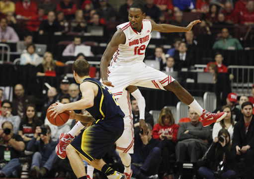 Senior forward Sam Thompson (12) leaps in the air while playing defense during a game against Michigan on Jan. 13 at the Schottenstein Center. OSU won, 71-52. Credit: Kelly Roderick / Lantern photographer