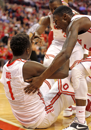 Freshman forward Jae'Sean Tate (1) is helped to his feet by redshirt-freshman guard Kam Williams during a game against Indiana on Jan. 25 at the Schottenstein Center. OSU won, 82-70.  Credit: Samantha Hollingshead / Lantern photographer