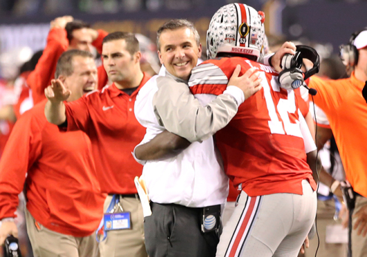 Coach Urban Meyer (in white) embraces redshirt-sophomore quarterback Cardale Jones (12) during the College Football Playoff National Championship on Jan. 12 in Arlington, Texas. OSU beat Oregon, 42-20. Credit: Mark Batke / Photo editor