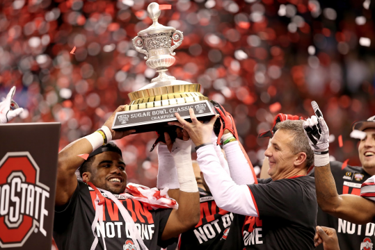 Sophomore running back Ezekiel Elliott (left) and coach Urban Meyer (right) lift the 2015 Allstate Sugar Bowl trophy into the air following OSU's 42-35 win over Alabama on Jan. 1 in New Orleans. Credit: Mark Batke / Photo editor