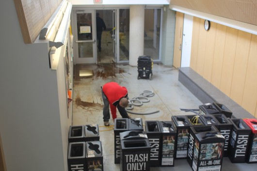 A maintenance worker cleans up some of the water damage in Scott Laboratory on Feb. 20. A fire sprinkler head froze and broke, causing flooding and water damage in the basement of the building. Credit: Robert Scarpinito / Lantern reporter