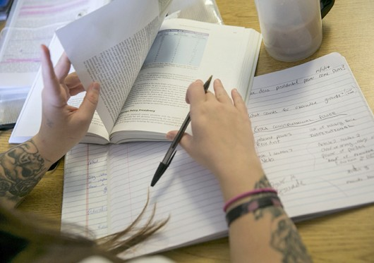 An inmate pages through a book in a government class. Credit: Courtesy of TNHS