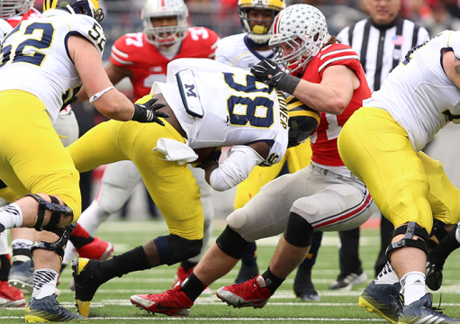 OSU sophomore defensive lineman Joey Bosa (right) sacks Michigan redshirt-senior quarterback Devin Gardner during a Nov. 29 game at Ohio Stadium. OSU won, 42-28. Credit: Mark Batke / Photo editor