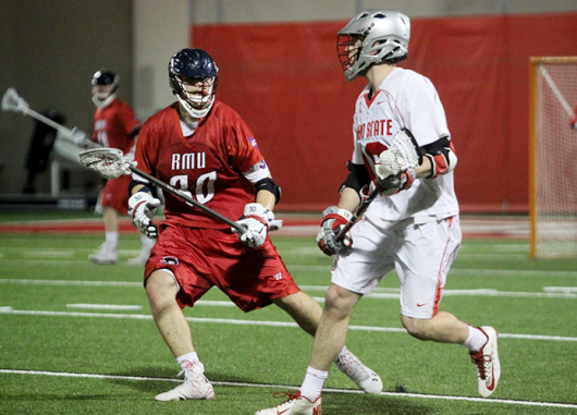 Senior midfielder Jesse King (right) carries the ball during a game against Robert Morris on Feb. 10 at the Woody Hayes Athletic Center. OSU won, 10-6. Credit: Molly Tavoletti / Lantern reporter