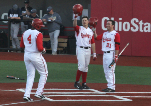 Sophomore outfielder Ronnie Dawson (4) is welcomed in to home plate by junior infielder Troy Kuhn (5) and redshirt-junior infielder Nick Sergakis (21) before scoring an OSU run. The Buckeyes beat in-state opponent, Akron, 9-4, on March 25 at Bill Davis Stadium in Columbus. Credit: Ethan Scheck / Lantern photographer