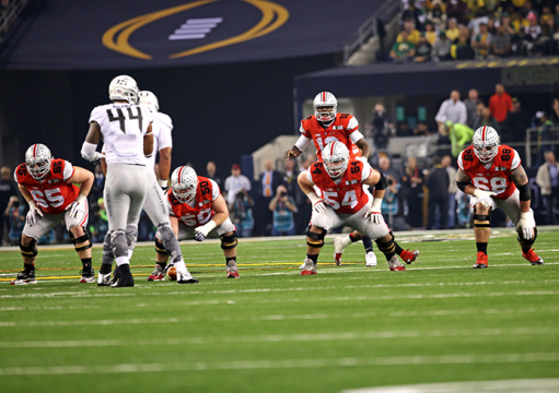 Then-redshirt-sophomore quarterback Cardale Jones (12) lines up behind members of the offensive line during the College Football National Championship game against Oregon on Jan. 12 in Arlington, Texas. OSU won, 42-20.  Credit: Mark Batke / Photo editor