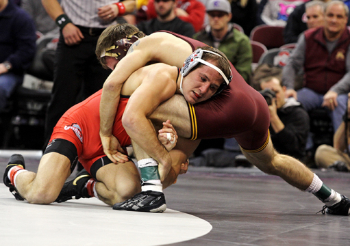 Redshirt-senior Logan Stieber (left) wrestles against Minnesota on Feb. 6 at the Schottenstein Center. OSU won, 22-13. Credit: Samantha Hollingshead / Lantern photographer