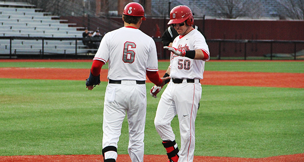 Sophomore infielder L Grant Davis (50) shakes hands with assistant coach Chris Holik (6) during a game against Louisville on April 14 at Bill Davis Stadium. OSU won, 2-0. Credit: Ryan Cooper / Lantern Photographer