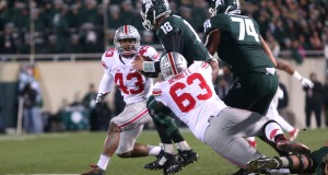 Then-OSU senior defensive lineman Michael Bennett (63) sacks Michigan State redshirt-junior quarterback Connor Cook (18) during a Nov. 8 game in East Lansing, Mich. OSU won, 49-37. Credit: Mark Batke / Lantern Photographer