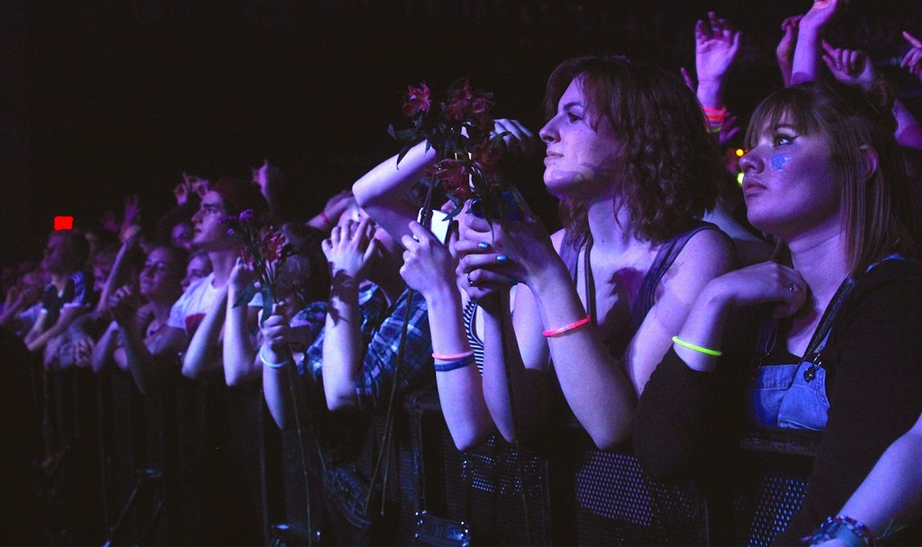 Fans at the LC Pavilion hold flowers thrown out to them by opening act, Waters. Credit: Elizabeth Tzagournis / Lantern photographer