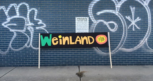 A sign, which supporters carried to the new mural's unveiling, leans against a graffitied building. Credit: Nick Roll / Lantern Reporter