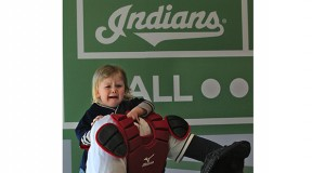 Two-year-old Finn David from Rocky River, Ohio, isn't too sure he wants to have his picture taken as a catcher inside the Kids Clubhouse area in the new Right Field District area at Progressive Field during the Cleveland Indians' home opener against the Detroit Tigers on April 10, in Cleveland. Credit: Courtesy of TNS