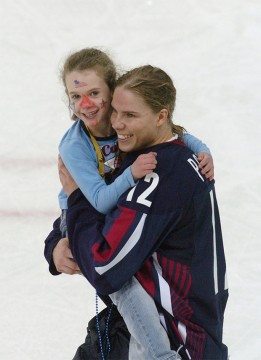 USA's Jenny Potter (12), of Anoka, Minnesota, carries her daughter Madison after the USA women's hockey team beat Finland 4-0 to win the bronze medal at the 2006 Winter Olympics in Turin, Italy, on Monday, February 20, 2006. Credit: Courtesy of TNS
