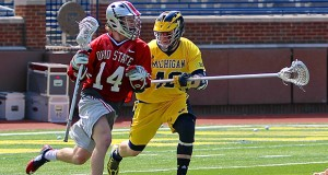 OSU junior attacker Carter Brown (14) attempts to move past a Michigan defender during an April 12 game in Ann Arbor, Mich. OSU won, 13-8. Credit: Molly Tavoletti / Lantern Reporter