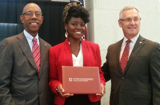 Youngstown State University President Jim Tressel (right) and University President Michael Drake (left) award Dorianeh Stanford with a certificate of completion Aug. 6 at the 2015 Ohio Export Internship Program Showcase. Credit: Michael Huson / Campus Editor