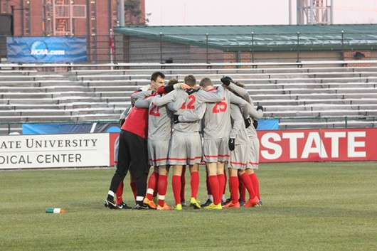 OSU mens soccer players gather in a huddle during a game. Credit: Lantern File Photo