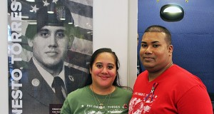 Oralia, Omar's sister and Sam, Oralia's husband pose in front of a photo of Omar Ernesto Torres in Torres House on August 22 in Columbus, Ohio. Photo Credit: Michael Huson / Campus Editor