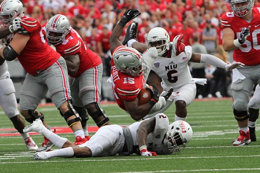 OSU junior running back Ezekiel Elliott (15) falls to the ground after a carry in a game against Northern Illinois on Sept. 19 at Ohio Stadium. OSU won, 20-13. Credit: Samantha Hollingshead / Photo Editor