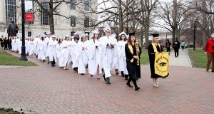 "A chapter of the Mortar Board Society carries the ""Golden Torch"" for the Golden Torch Award across campus. Credit: Courtesy of LoLynn Giancola"