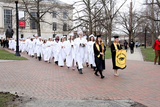 """A chapter of the Mortar Board Society carries the """"Golden Torch"""" for the Golden Torch Award across campus. Credit: Courtesy of LoLynn Giancola"""