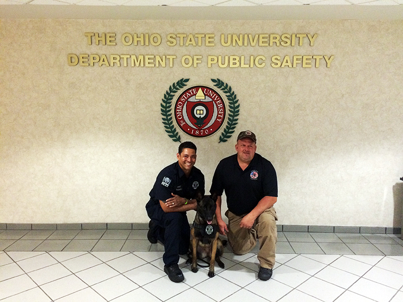 University Police Officer Bryan Thompson (left) and the Mike Pennington (right), president of Storm Dog Tactical, with Canine Ena at Blankenship Hall. Credit: Aubrey Cornwell / Lantern reporter