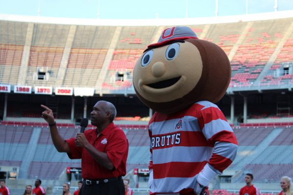 """Brutus Buckeye and Ohio State Athletic Director Gene Smith participate during the """"Buckeye Kick-Off"""" on August 27 at Ohio Stadium. Credit: Ed Momot / For The Lantern"""