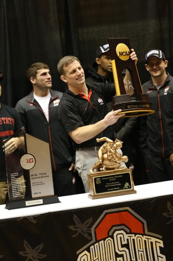 Coach Tom Ryan lifts the the Buckeyes' national championship trophy as fans applaud during a national championship celebration for the OSU wrestling team on March 28 at St. John Arena. Credit: Lantern File Photo