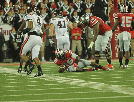 Then-redshirt freshman quarterback J.T. Barrett (16) lies on the ground after being tackled during a game against Virginia Tech Sept. 6 at Ohio Stadium. OSU lost, 35-21. Credit: Lantern File Photo