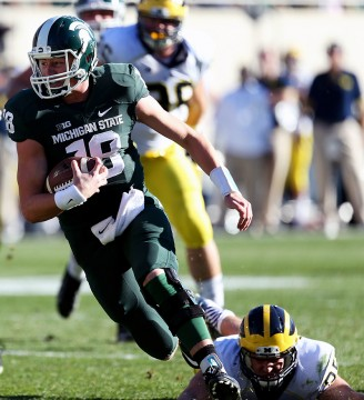 Michigan State's Connor Cook runs past Michigan's Joe Bolden during first quarter action on Saturday, Oct. 25,2014 at Spartan Stadium in East Lansing, Mich. Michigan State won 35-11. Credit: Courtesy of TNS