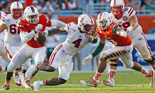 Miami's Al-Quadin Muhammad (8) and Trent Harris (33) chase and sack Nebraska quarterback Tommy Armstrong Jr. (4) in the third quarter at Sun Life Stadium in Miami Gardens, Fla., on Sept. 19. Miami won, 36-33, in overtime. Credit: Courtesy of TNS