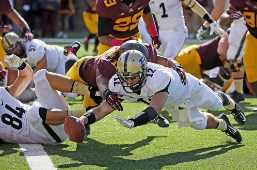 Purdue's quarterback Austin Appleby (12) jumped toward the goal line for a touchdown in the third quarter as the Minnesota Gophers took on the Purdue Boilermakers, Saturday, Oct. 18, 2014 at TCF Bank Stadium in Minneapolis. Minnesota. Credit: Courtesy of TNS