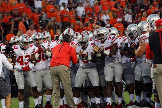 Coach Urban Meyer and members of OSU football team before a game against Virginia Tech on September 7 in Blacksburg, Virginia. OSU won 42-24. Credit: Samantha Hollingshead / Photo Editor