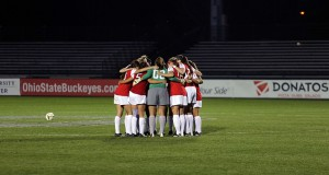 OSU women's soccer players gather in a huddle during a match Oct. 24, 2014 against Iowa at Jesse Owens Memorial Stadium. Credit: Lantern File Photo