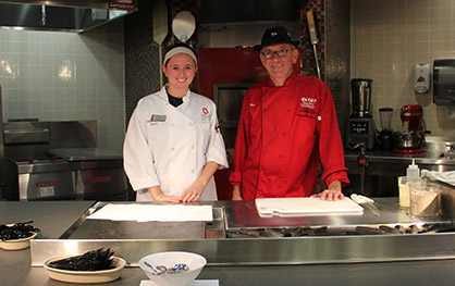 Chef Marc Dullin (right) and his teaching assistant Victoria Figliomeni, a fourth-year in hospitality management. Credit: Samantha Hollingshead / Photo Editor