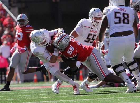 Then redshirt sophomore defensive end Tyquan Lewis (59) drags down Maryland redshirt junior quarterback Perry Hills on Oct. 10. OSU won 49-28. Credit: Lantern file photo