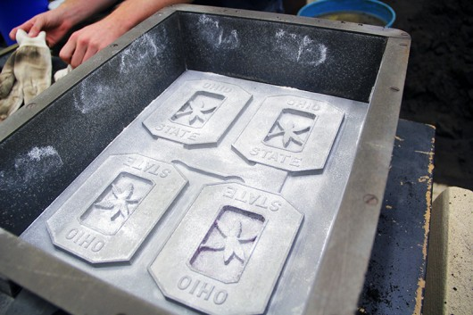 Students in the OSU Foundry Club prepare the Block O mold for pouring on Tuesday, Oct. 7 in Watts Hall by using talcum powder to prevent sticking. Credit: Ian Bailey / Lantern Reporter