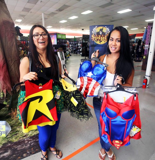 Women show off halloween costumes at a Halloween store. Credit: Courtesy of TNS