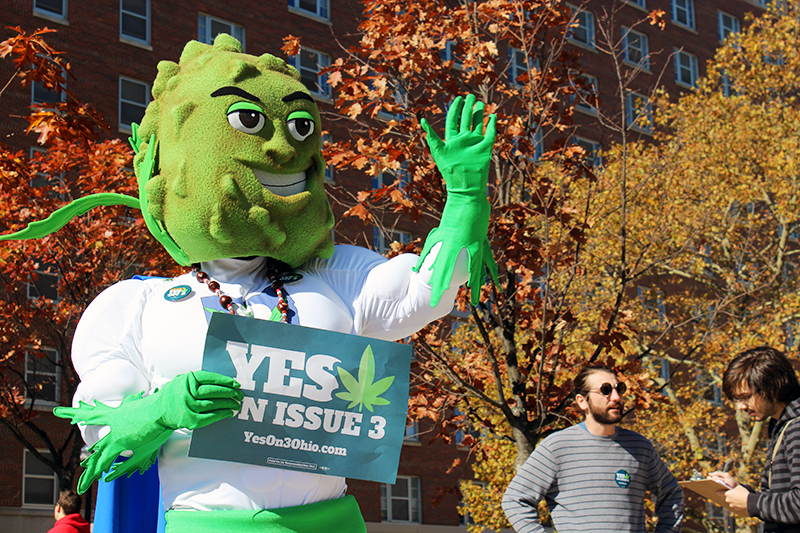 Buddie, the marijuana mascot for ResponsibleOhio's marijuana legalization campaign, greets OSU students on Oct. 26. Credit: Michael Huson | Campus Editor